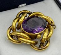 A Pinchbeck brooch with safety chain and central purple stone.