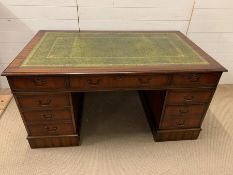 A large pedestal desk with green leather top flanked by drawers (H77cm W150cm D90cm)