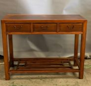 An oriental style hard wood console table with three drawers to centre and shelf (H80cm W100cm