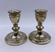 A Pair of silver squat candlesticks by A T Cannon Limited and hallmarked Birmingham 1977.