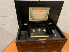 A 19th century rosewood veneered and ebonised inlaid cylinder music box, lockable with key