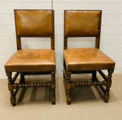 A pair of oak chairs with leather seats