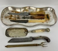 A selection of bone and horn handled serving items to include carving set on a silver plated tray.