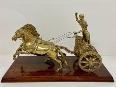 A Brass desk ornament on mahogany plinth, figure of a roman chariot with two horses,