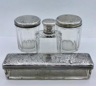 A selection of four matching white metal lidded glass items from a vanity set