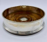 A silver bottle coaster by WEV, hallmarked for London 2000