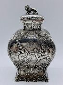 A silver tea caddy with repousse design and lion finial by Samuel Boyce, hallmarked for Chester 1903