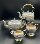 A Victorian silver teapot, teapot on stand, sugar bowl and milk jug by Charles Stuart Harris,