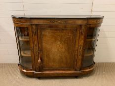 A French style figured walnut credenza, gilt work, bowed glass cabinets, breakfront with central