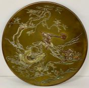 An oriental brass and copper plate, on feet depicting warriors fighting among the lotus flowers