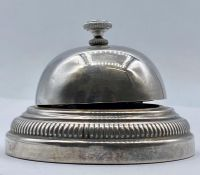 A white metal desk bell, indistinct mark to base.