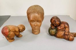 Three carved wooden figures, one bust of a women, one sleeping baby and one of a figure praying