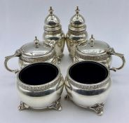 A silver cruet set with two peppers, two salts and two mustards with blue glass liners by A E Poston