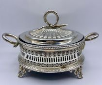 A Silver bonbon dish, with lid and blue glass liner, snake themed finial and handles on four feet.
