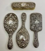 A selection of three silver backed vanity mirrors and one brush, various designs and hallmarks.