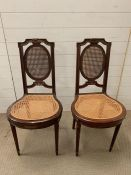 Two bedroom chairs with fluted legs and cane seats