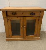 A pine side cupboard with glazed double doors (H82cm W89cm D37cm)
