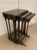 A set of four rosewood nesting tables on turned supports