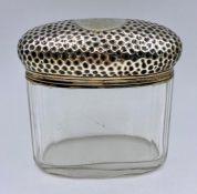 A silver lidded glass jar, with a Birmingham hallmark.