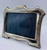 An easel backed silver photo frame, with indistinct hallmarks (19cm x 14 cm)