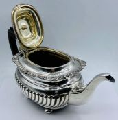 A substantial silver teapot, (Total weight 695g) on four feet, by George Nathan & Ridley Hayes and