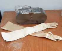 A hard plastic handbag with long gloves
