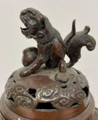 A Chinese urn or censor with Foo dog finial.