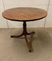 An oak center table on turned column, terminating on scroll feet, tilt top ( Diameter 84cm x 72cm