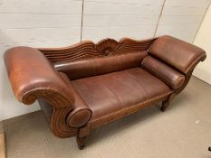 A New York style mahogany and leather sofa with scrolling ends and studs, two leather bolsters (