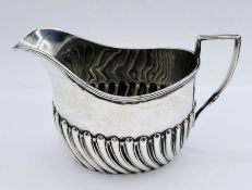 A silver milk jug by Harrison Brothers & Howson (George Howson), hallmarked for Sheffield 1902 (