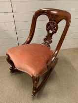 A mahogany rocking chair with pink upholstery