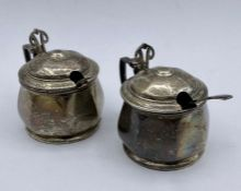 A pair of silver cruets AF with blue glass liners by Barker Brothers Silver Ltd, Birmingham 1938.