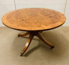 A Walnut center table, with burr walnut string inlay on sabre legs.