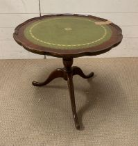 A tilt top side table with green leather top and scalloped edges