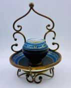 A porcelain inkwell with a geometric design in metal stand