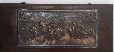 A brass relief on wood depicting a quadrigas race, signed: 'P.King' (after engraving) and dated 1909
