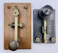 Two Morse code keys, one in Bakelite and the other wooden based.
