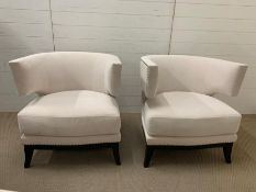 A pair of contemporary semi circular arm chairs with stud details