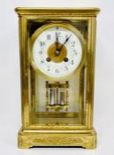 An eight day enamel faced eight day clock in a decorative engraved brass case.