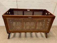 An oak carved cot with cane sides (H69cm W109cm D50cm)