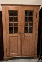 An Georgian pine cupboard with five shelves and part glazed doors