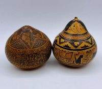 Two miniature Peruvian gourds, one intricately engraved with an folklore tale and one of women and