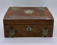 A wooden jewellery box with white metal decoration and cartouche