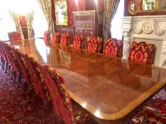 A Sixteen seat mahogany dining table with fourteen chairs and two carvers in red and gold. 540cm