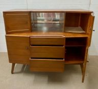 A Beautility teak side board consisting of four cupboards, three drawers and a sliding glass
