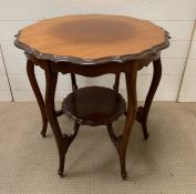 A scrolled edge mahogany two tier table (H67cm Dia68cm)