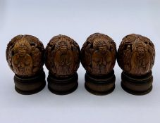 A Box of Four Antique Chinese carved walnuts on stands