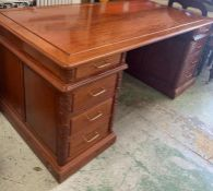 A rosewood pedestal desk with carving to door sides and turned metal handles (186cm x 90 cm x 78