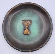 A metal wall plate with a Menorah.