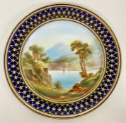 A mid 19th Century hand decorated Worcester style plate with blue and gilt border and lake scene to